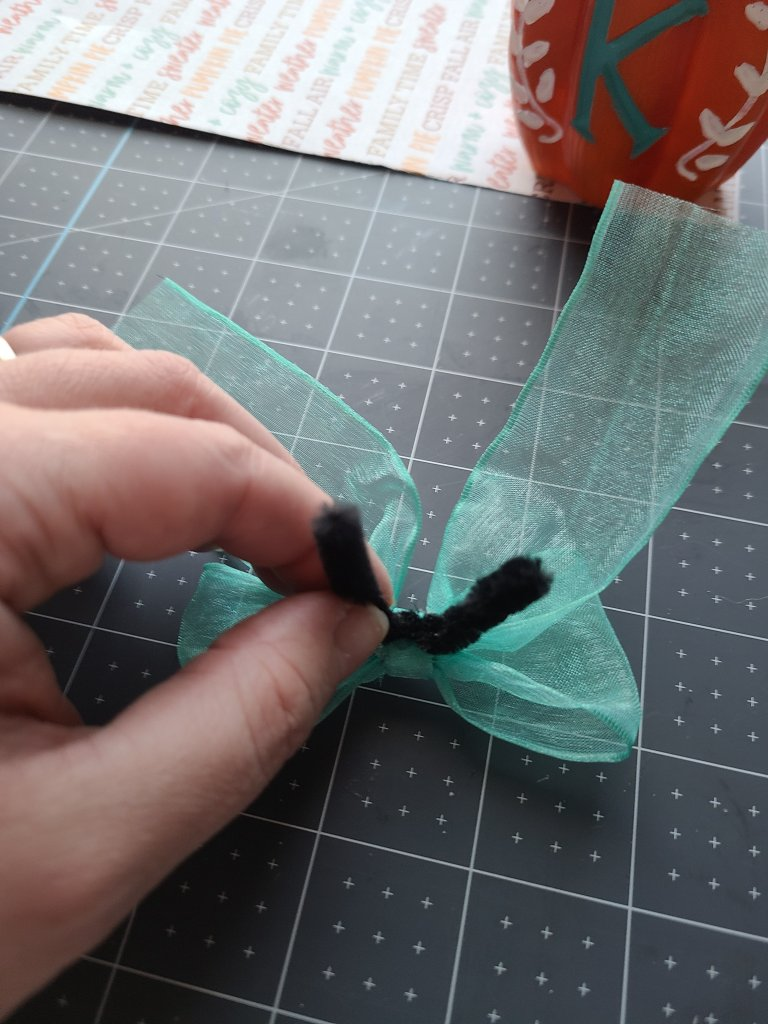 """Gluing 2"""" of a pipe cleaner to the back of the fall bows for the reversible Dollar Tree pumpkins."""