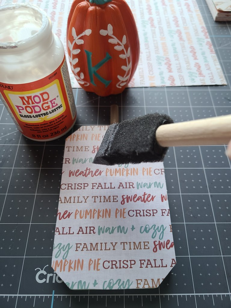 Mod Podge being applied on top of the fall themed cardstock on one of the reversible Dollar Tree pumpkins.