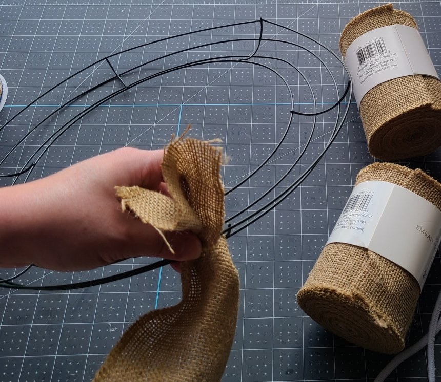 Slip the burlap through between the outer ring and the second ring.