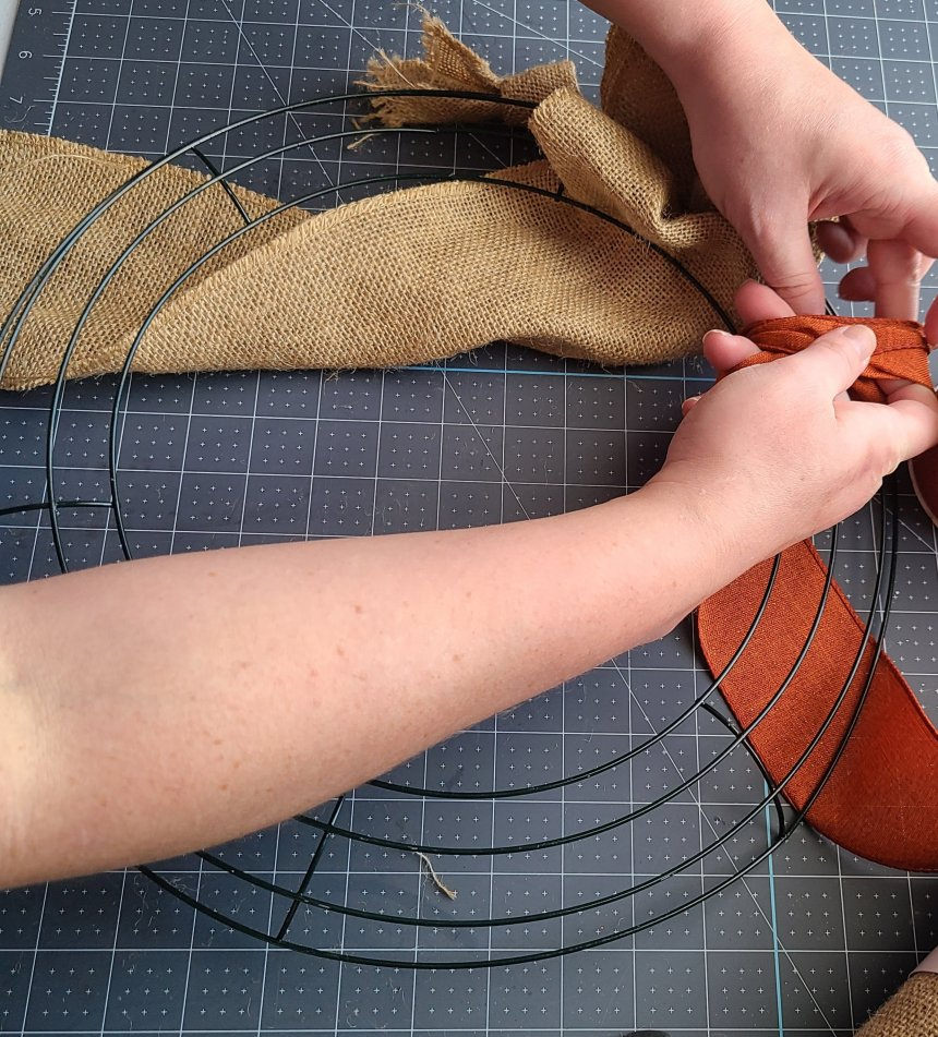 """Pulling the orange ribbon through the inner ring making a """"bubble"""" with it."""