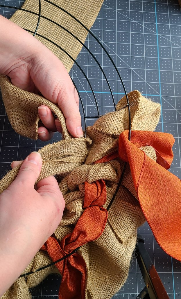 Pushing the start of a new roll of burlap through the rings on the burlap wreath.