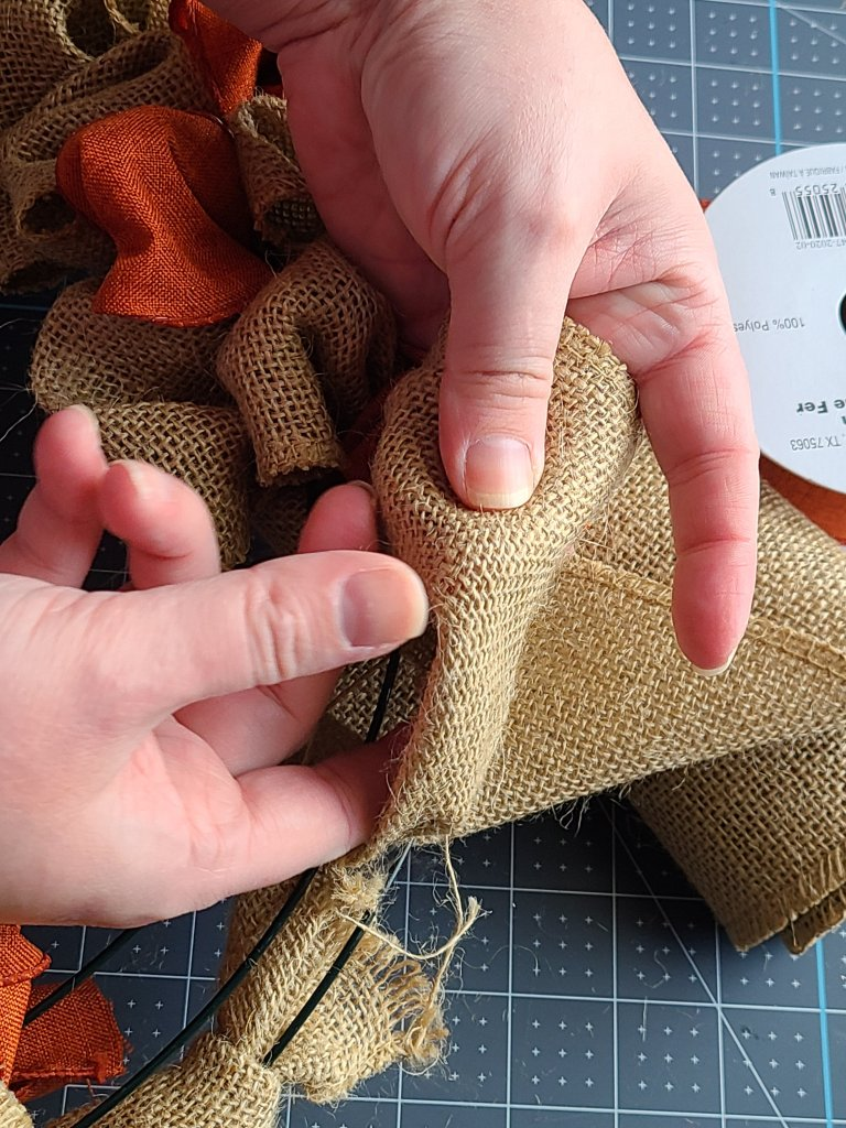 Pulling burlap through the outer ring on the burlap wreath.