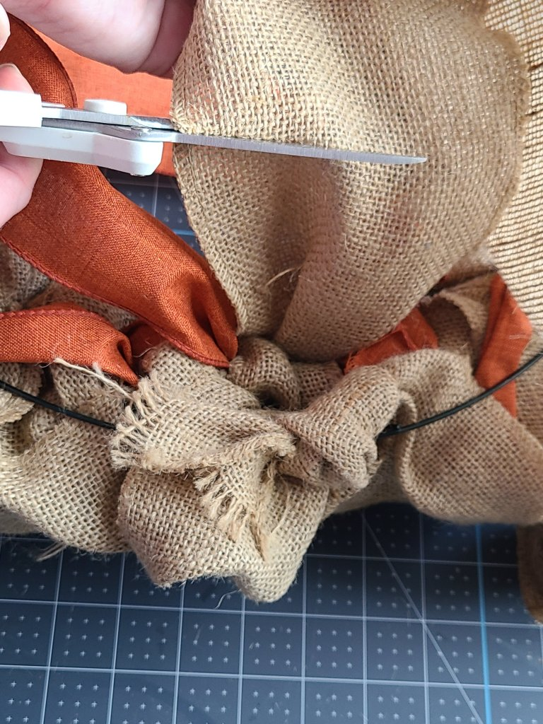 Using scissors to cut the end of the burlap from the rest of the roll.