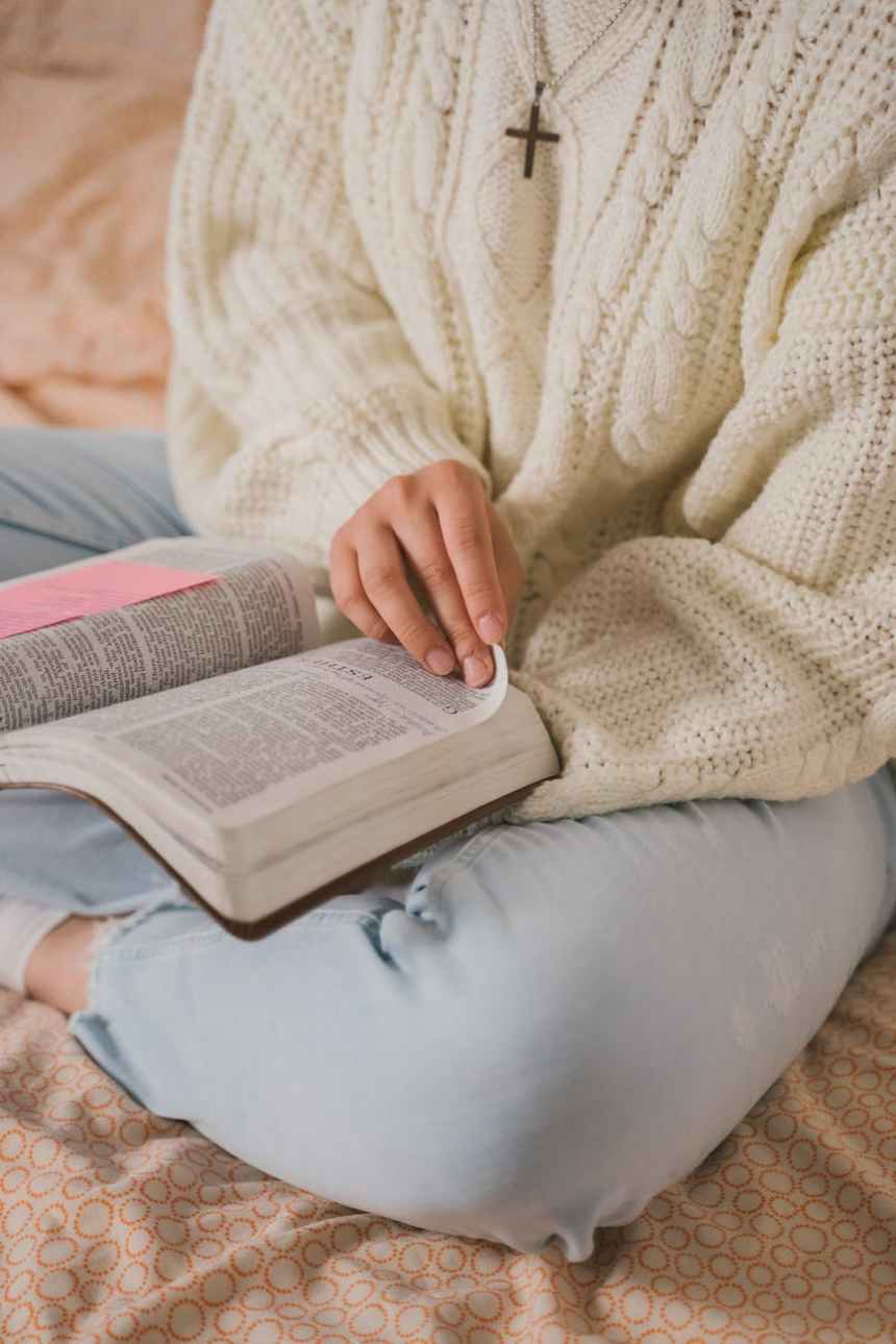 woman in white knit sweater reading book