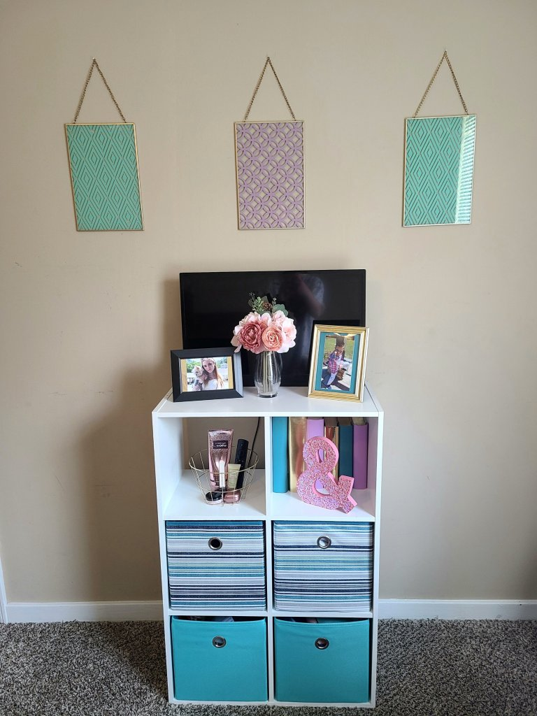 White shelving unit from the craft room makeover. Three wall art pieces hung above shelf, tv on top with two picture frames and a bouquet in front of the TV, decor in top two cubbies, and storage bins in bottom four cubbies.