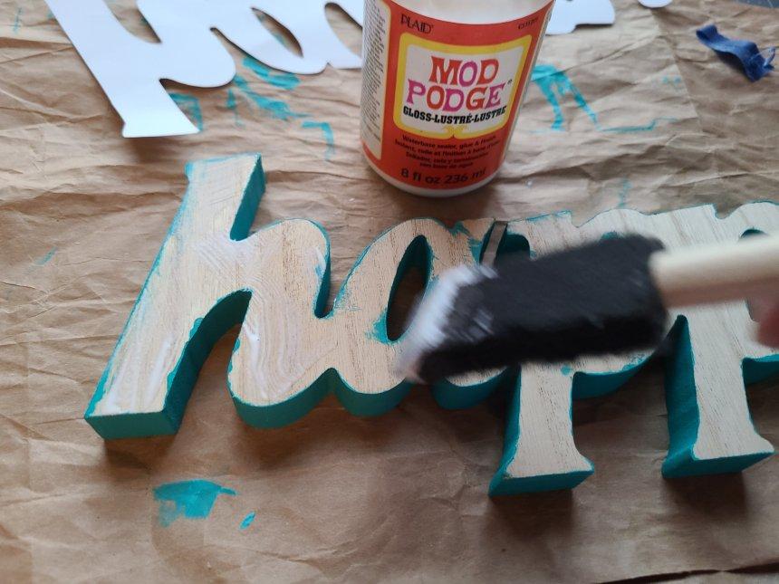 Using a foam brush to layer Mod Podge on the wood fall Dollar Tree DIY decor word.