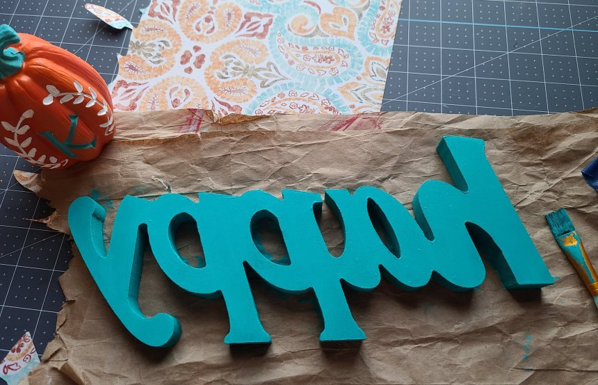 "The back of the fall Dollar Tree DIY decor ""happy"" painted aqua."