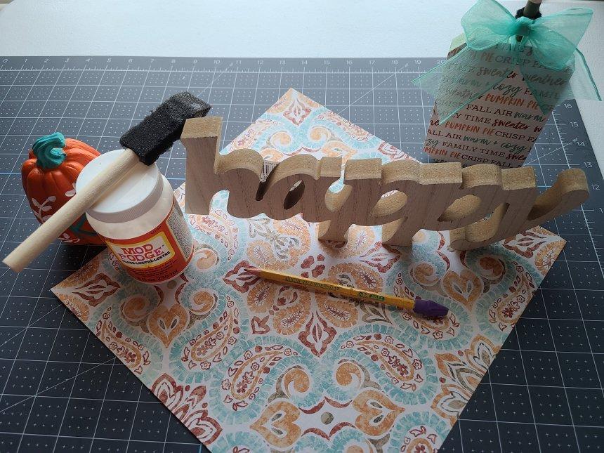 Fall Dollar Tree DIY decor supplies: wood word, Mod Podge, foam brush, pencil, & fall pattern paper.