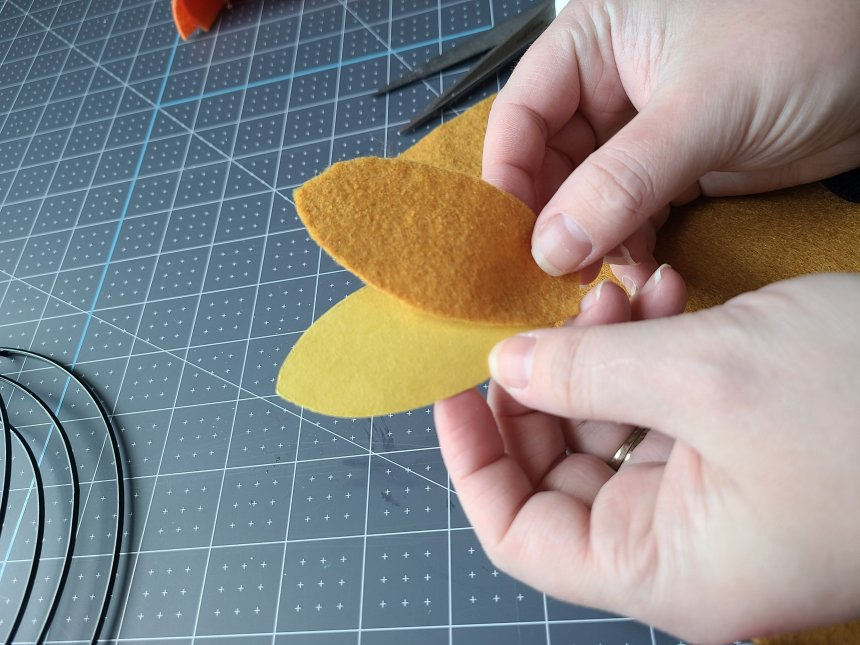 Showing completely cut out mustard felt leaf next to the paper leaf. It will be added to the felt leaf wreath.