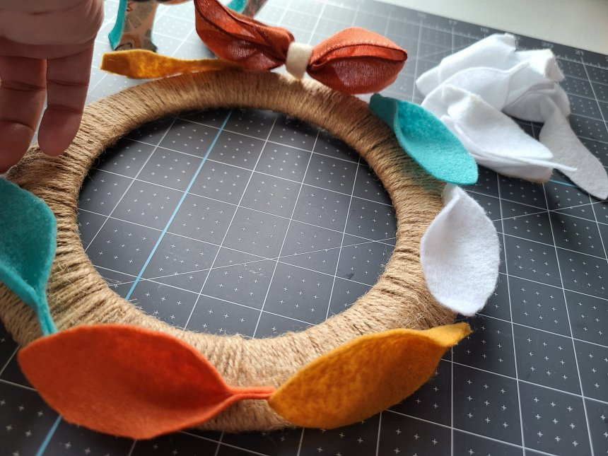 Wreath wrapped in twine with felt leaves being laid from just under the orange bow all around the felt leaf wreath.