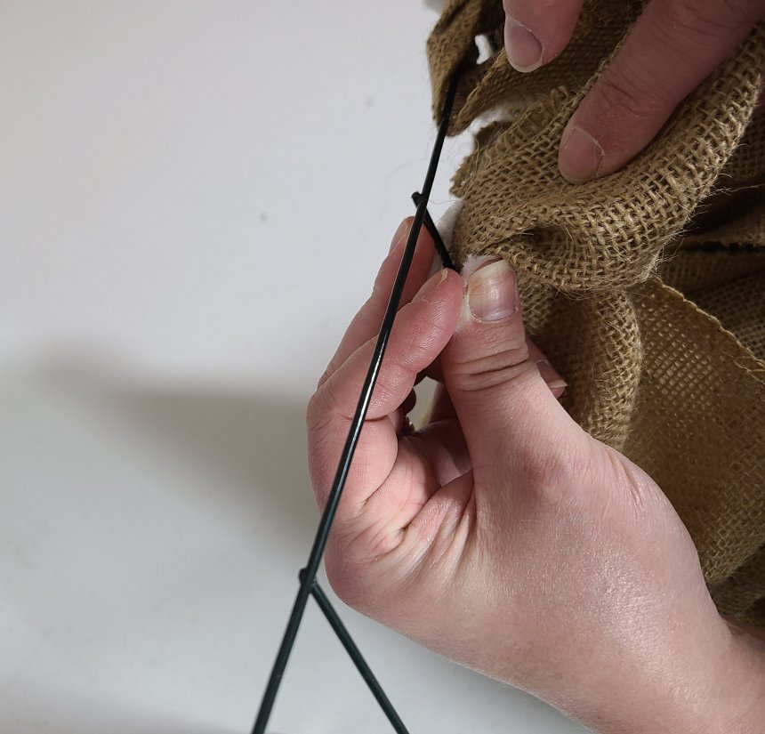 Attaching burlap to the bottom wire on the bottom triangle of the burlap witch hat wreath.