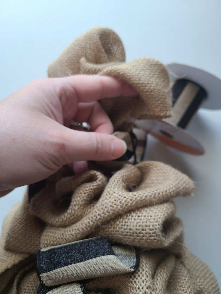 Pulling accent ribbon through the front of the burlap witch hat wreath to create bubbles.