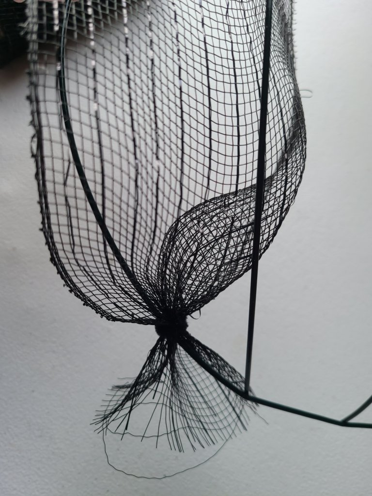 Black deco mesh attached to the Halloween pumpkin wreath form at the bottom just to the left of the vertical crossbar.
