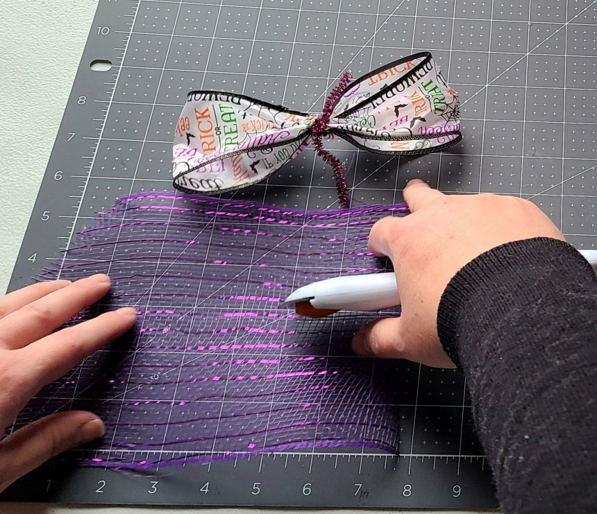 """Cutting an 8"""" piece of deco mesh from the purple roll. These will be rolled and added to the bow for the Halloween pumpkin wreath."""