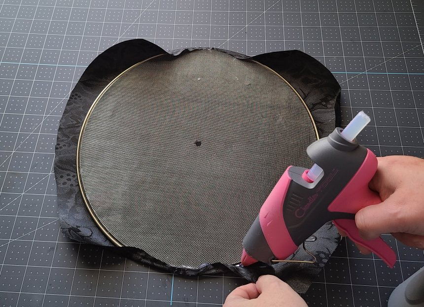 Adding hot glue along the wire of the splatter screen and folding the fabric over the edge. This will be one of the panels on the Halloween splatter screen pumpkin.