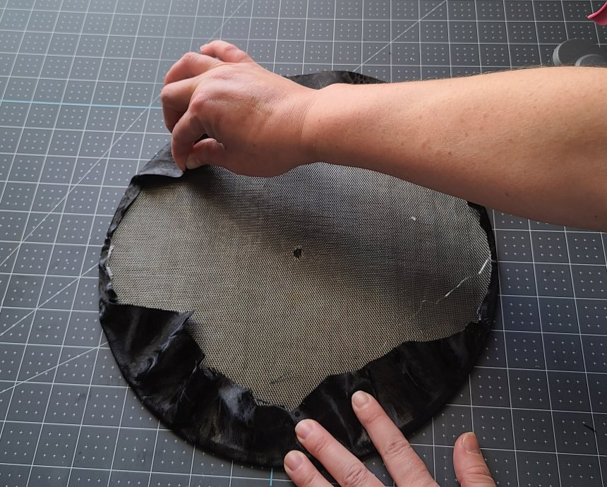Pulling the fabric taunt over the edge of the splatter screen on top of hot glue until it's completely covered and will become part of the Halloween splatter screen pumpkin.