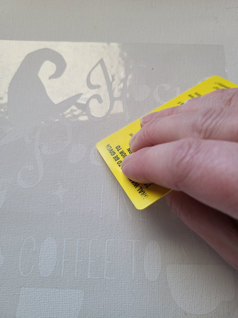 Using a credit card to scrape across the vinyl stencil on canvas to adhere it firmly to it.