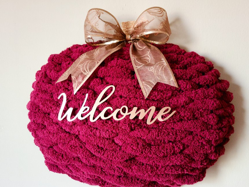 """Complete yarn pumpkin wreath: thick fluffy burgundy yarn woven through a pumpkin wire wreath frame, with the stem covered with copper ribbon, a copper pumpkin print bow, with the metal copper-colored word """"welcome"""" in the middle."""
