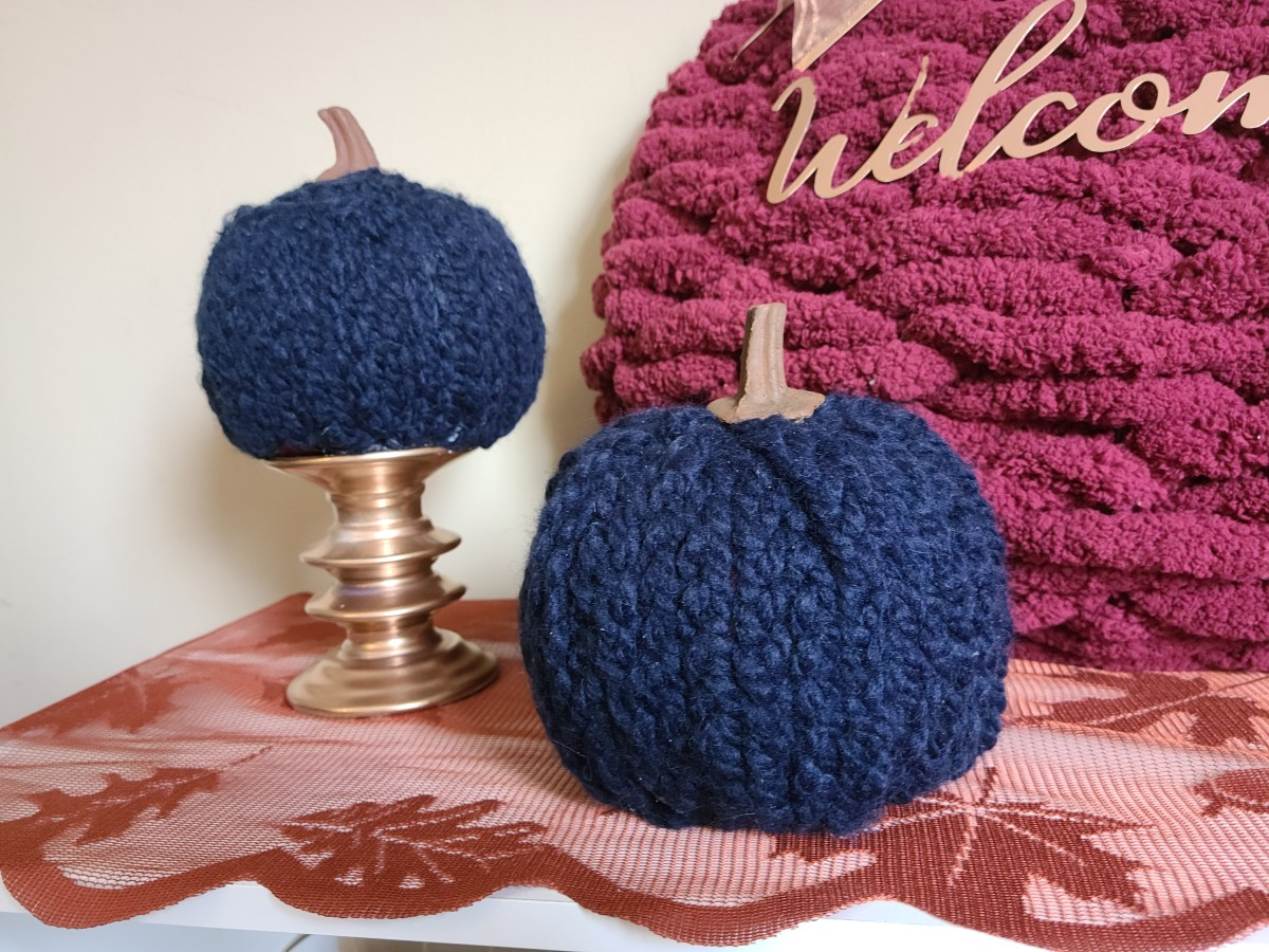 Two braided yarn pumpkins with the edge of a burgundy woven pumpkin wreath.