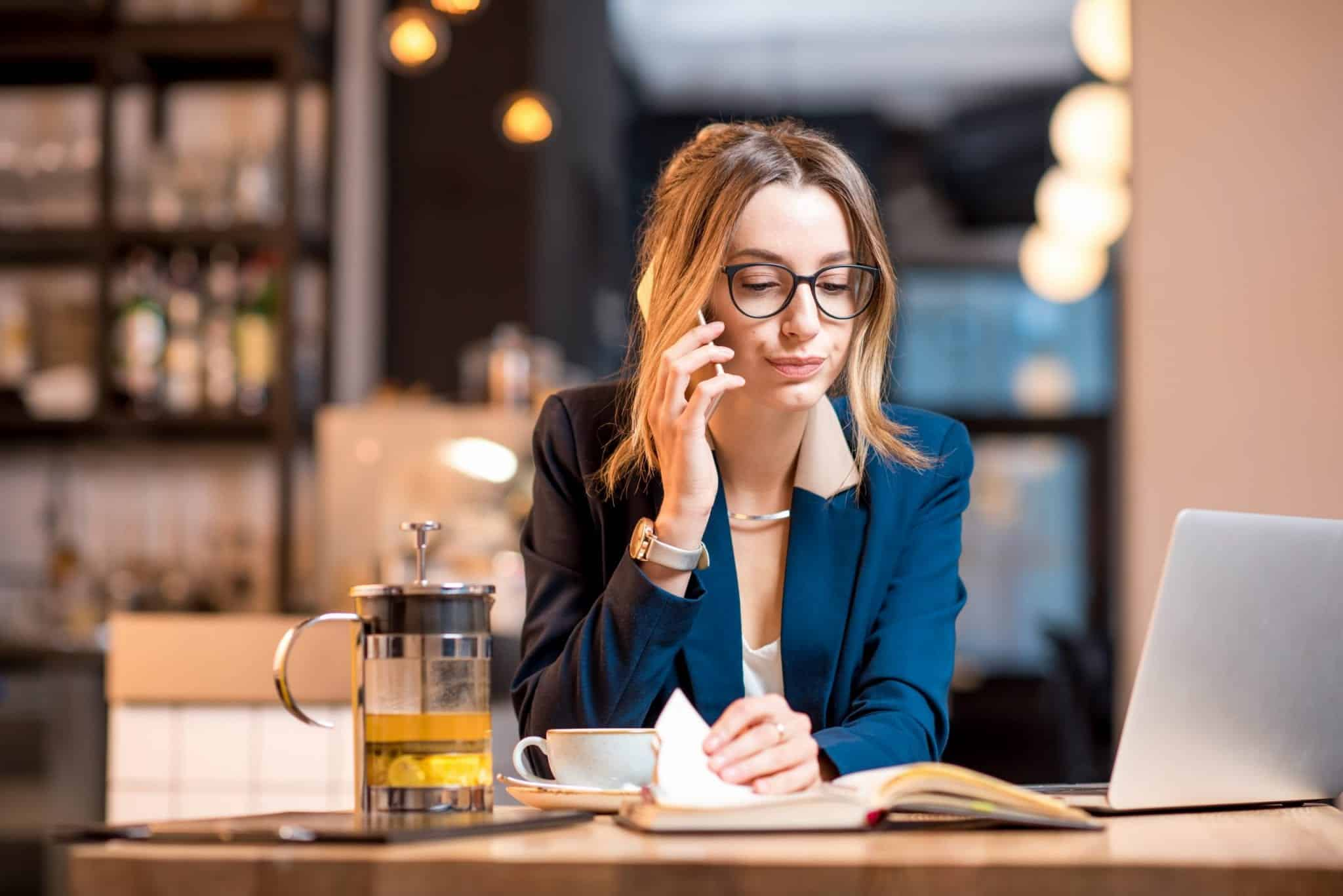 woman working on phone at coffee shop