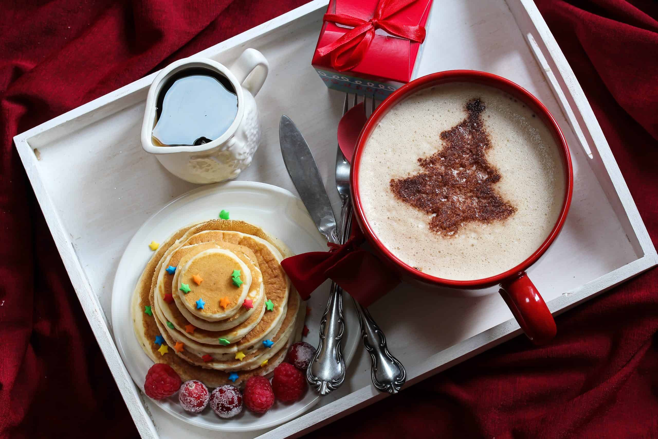 Christmas Breakfast on a tray pancakes and Coffee with chocolate dusting