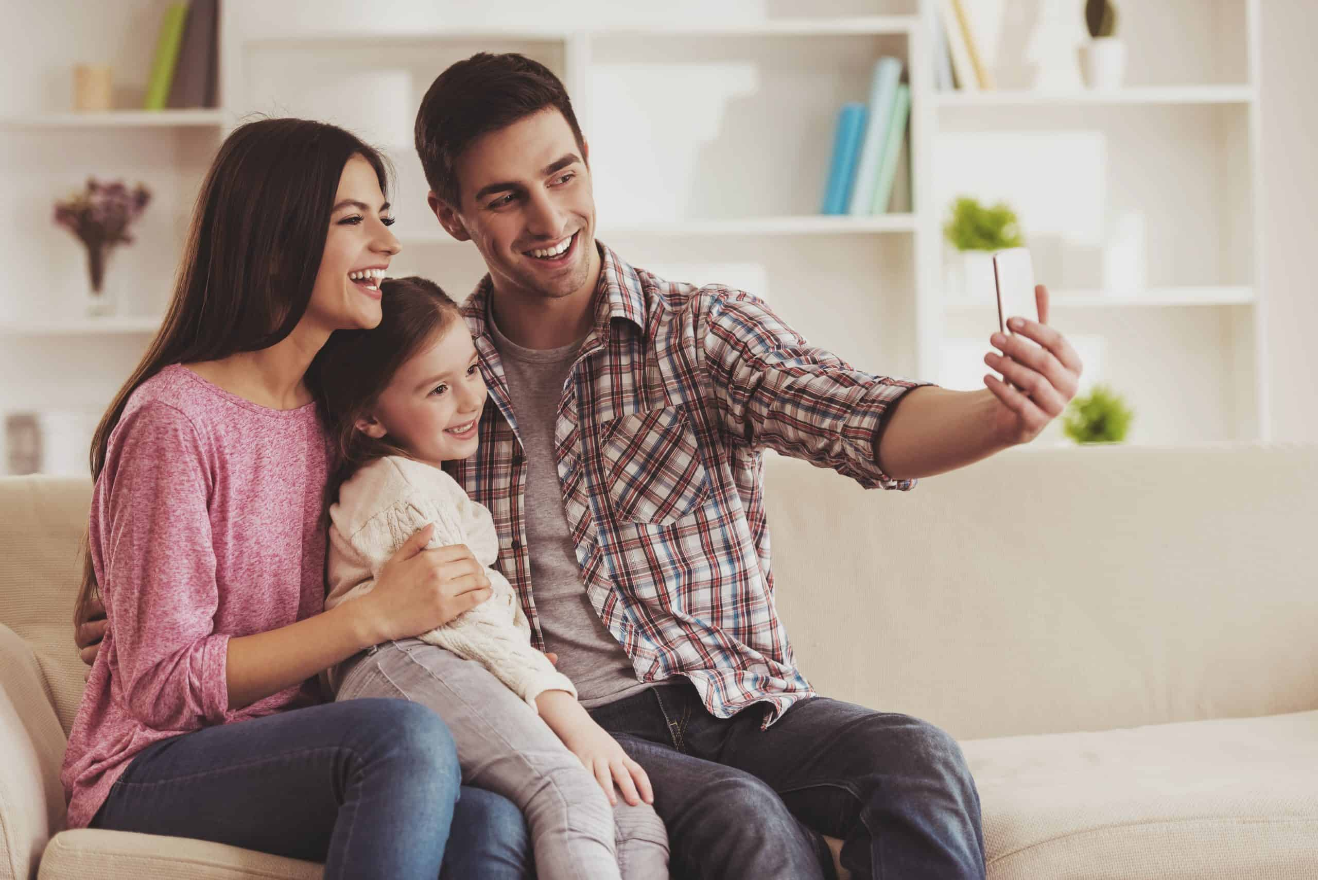 traveling with kids Family Members Making Selfie. Parents and Kid Sitting on Sofa. Portrait at Home. Family Concept. Smiling Parents. Child at Home. Little Daughter. Child in Hugging. People in the Room.