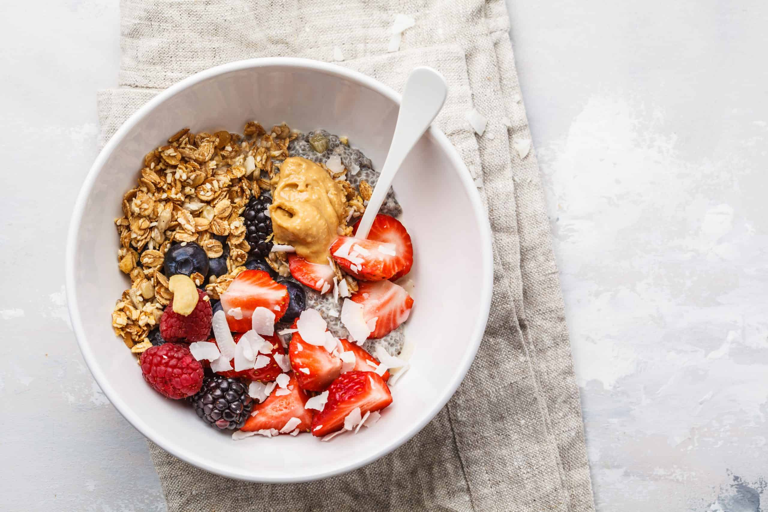 Berries, granola, milk, peanut butter breakfast in a white bowl. Healthy vegan food concept.