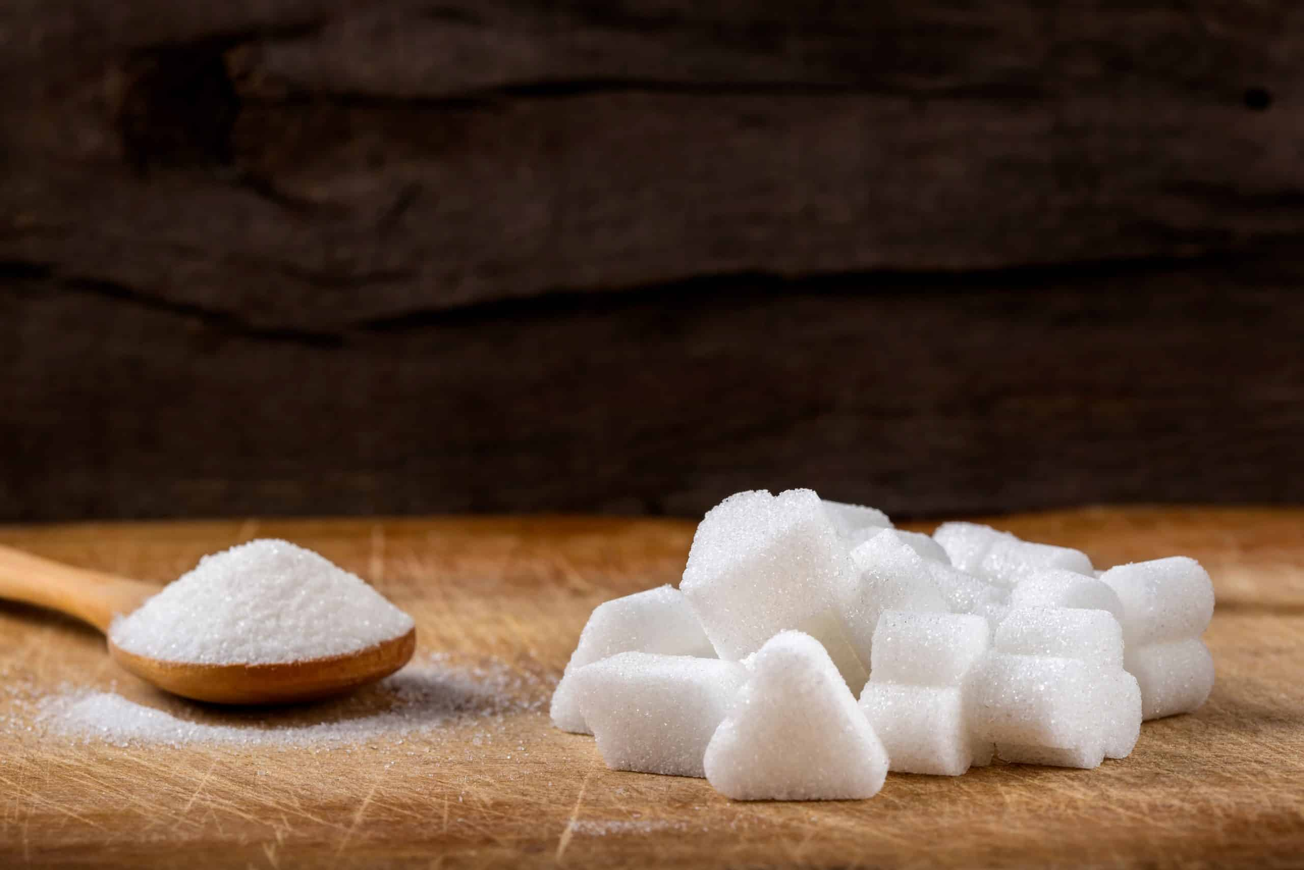 Heap of different sugar cubes shapes and one wooden spoon filled with sugar in background