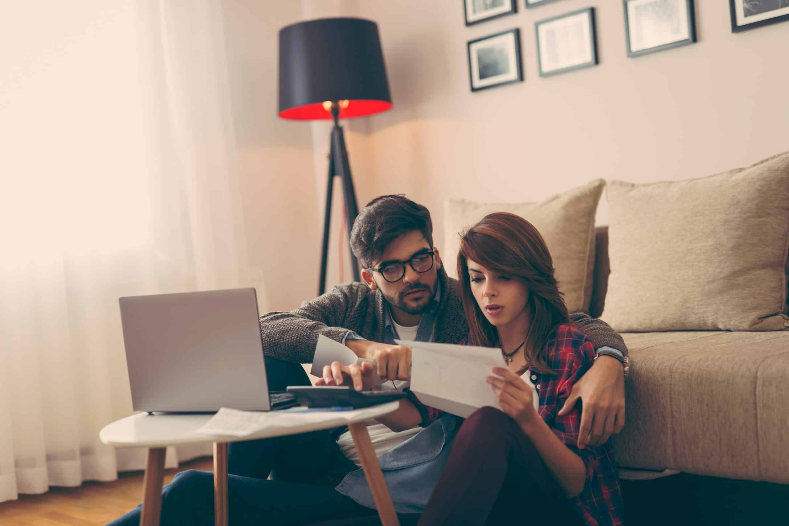 Young couple managing their family budget, going through receipts and paperwork and paying the mortgage and bills