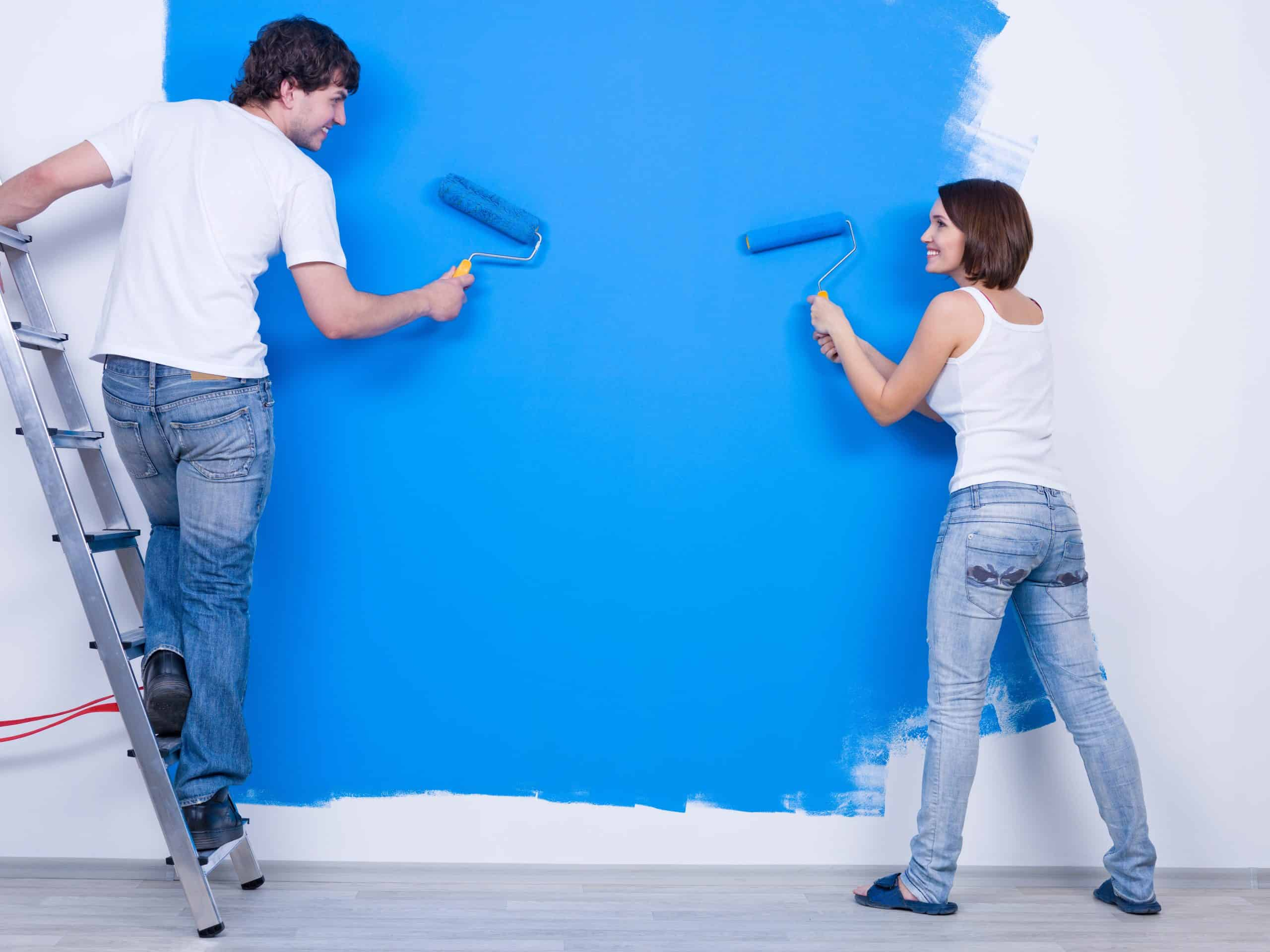 home renovation mistakes Young couple in casuals сoloring the wall in blue - rear view