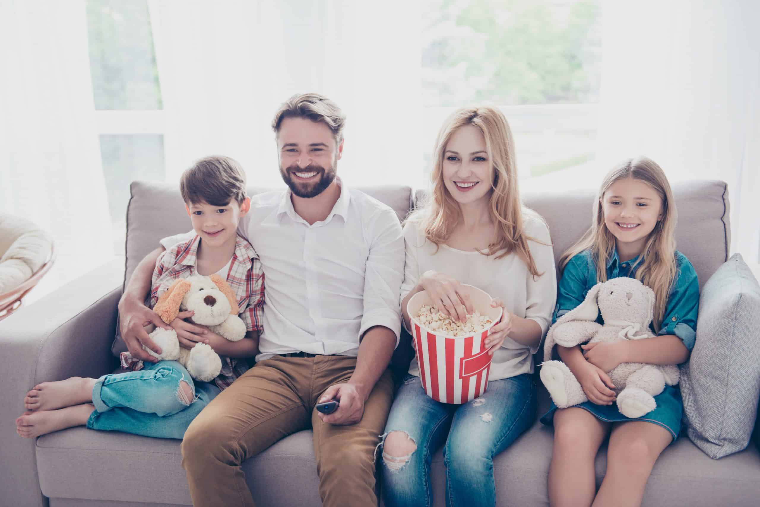 family holiday Young beautiful couple of blondie and brunette guy are watching family movie with kids, eating popcorn at light cozy home, smiling, enjoying