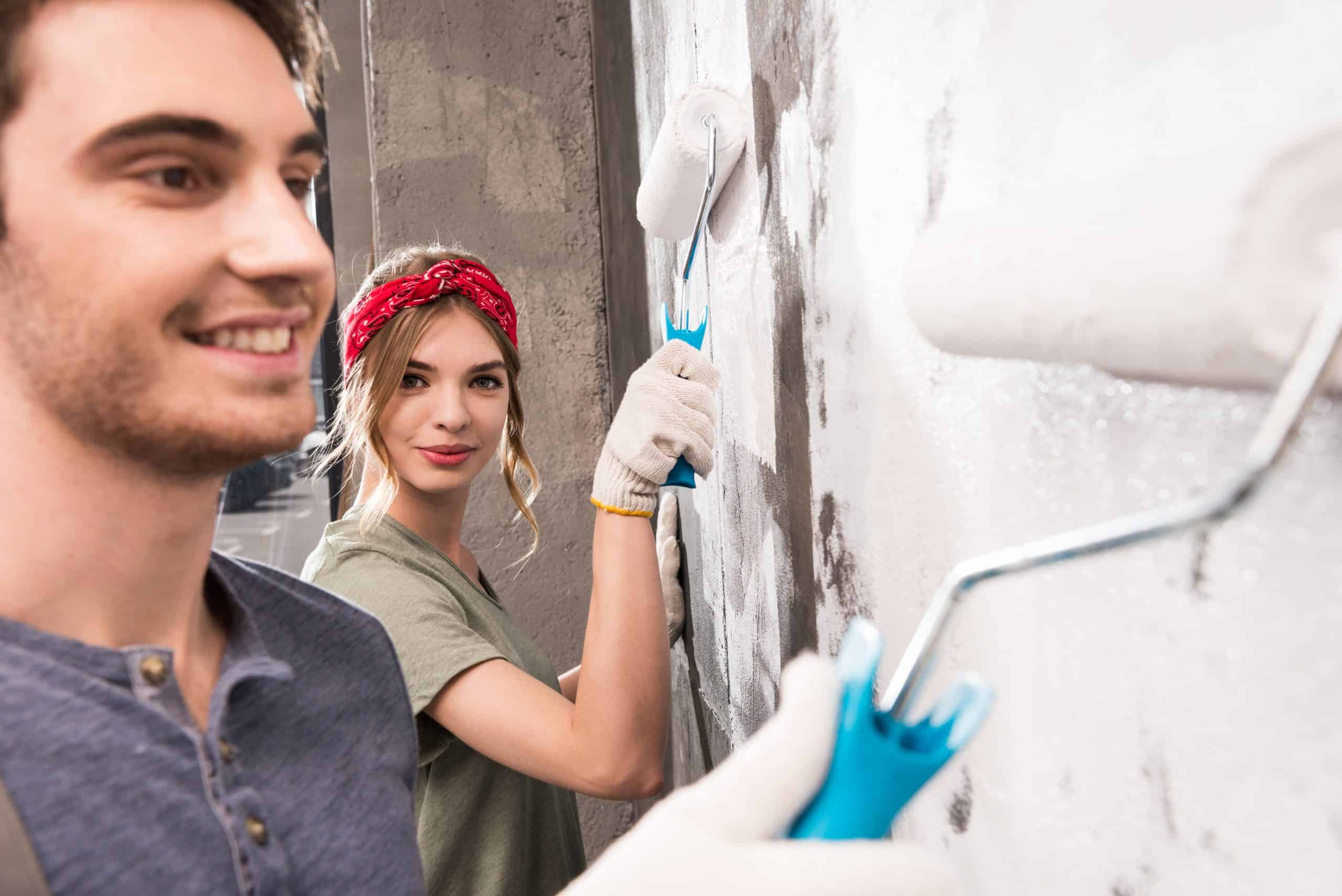 young couple painting wall together, renovation home concept