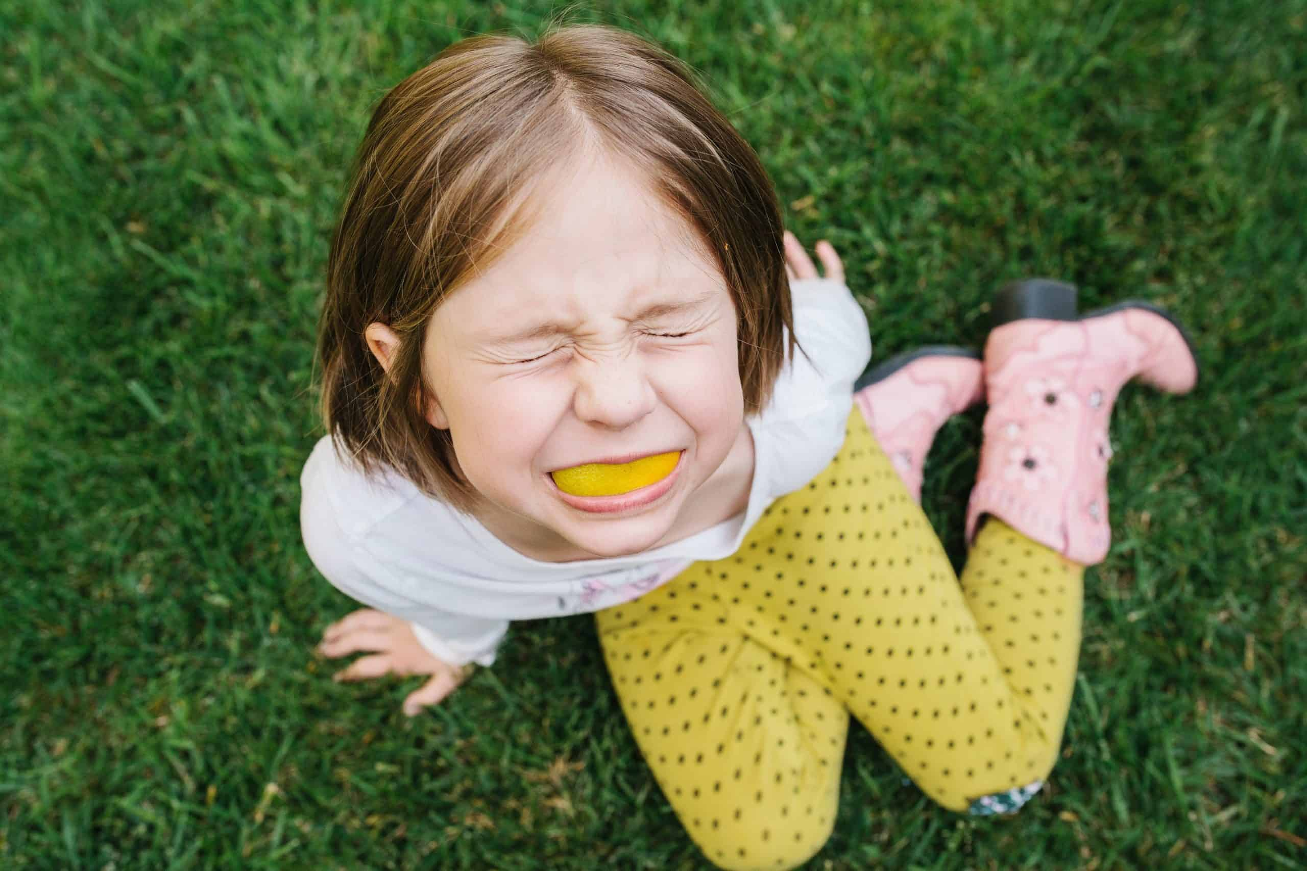 Close photograph of a girl with an orange peel in her mouth