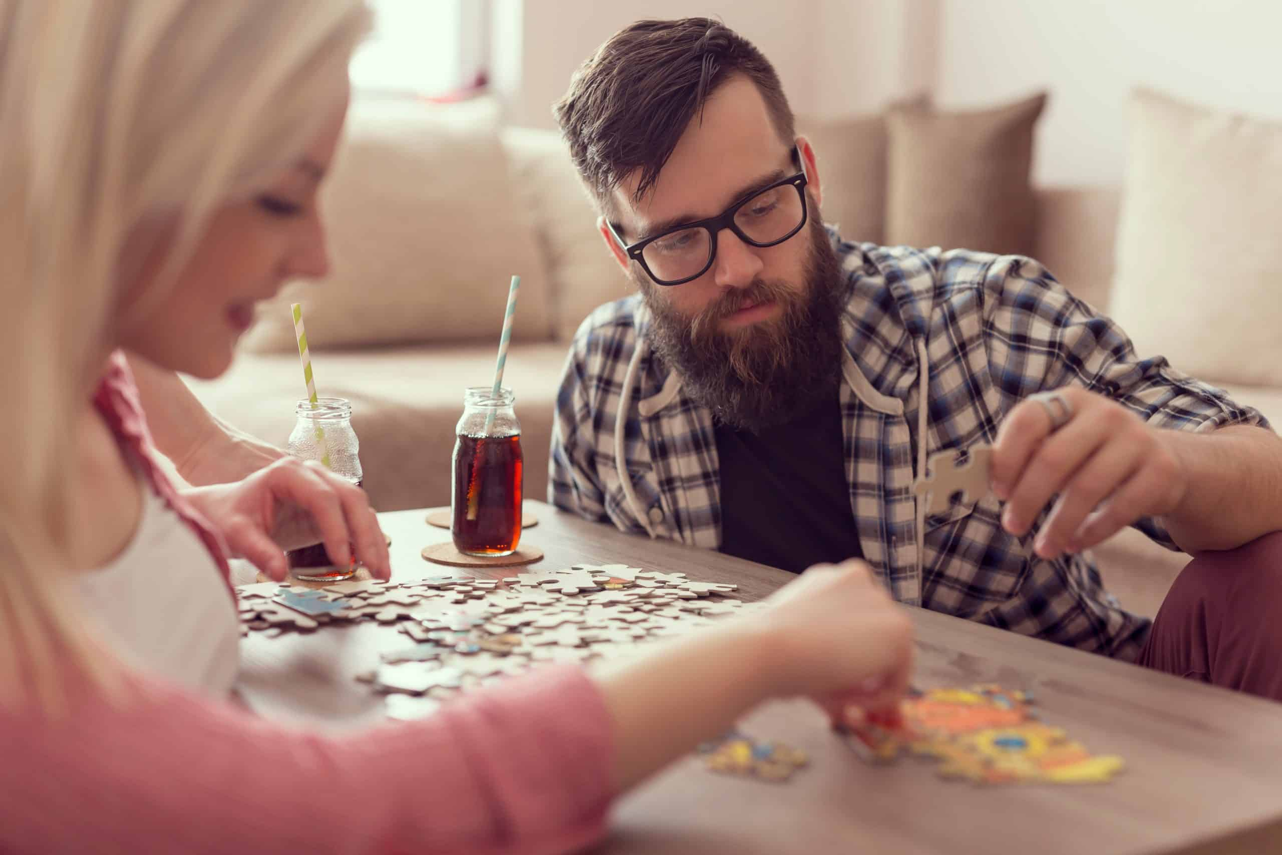 Couple in love sitting on the floor next to a table, solving a jigsaw puzzle problem and enjoying their leisure time activities family game