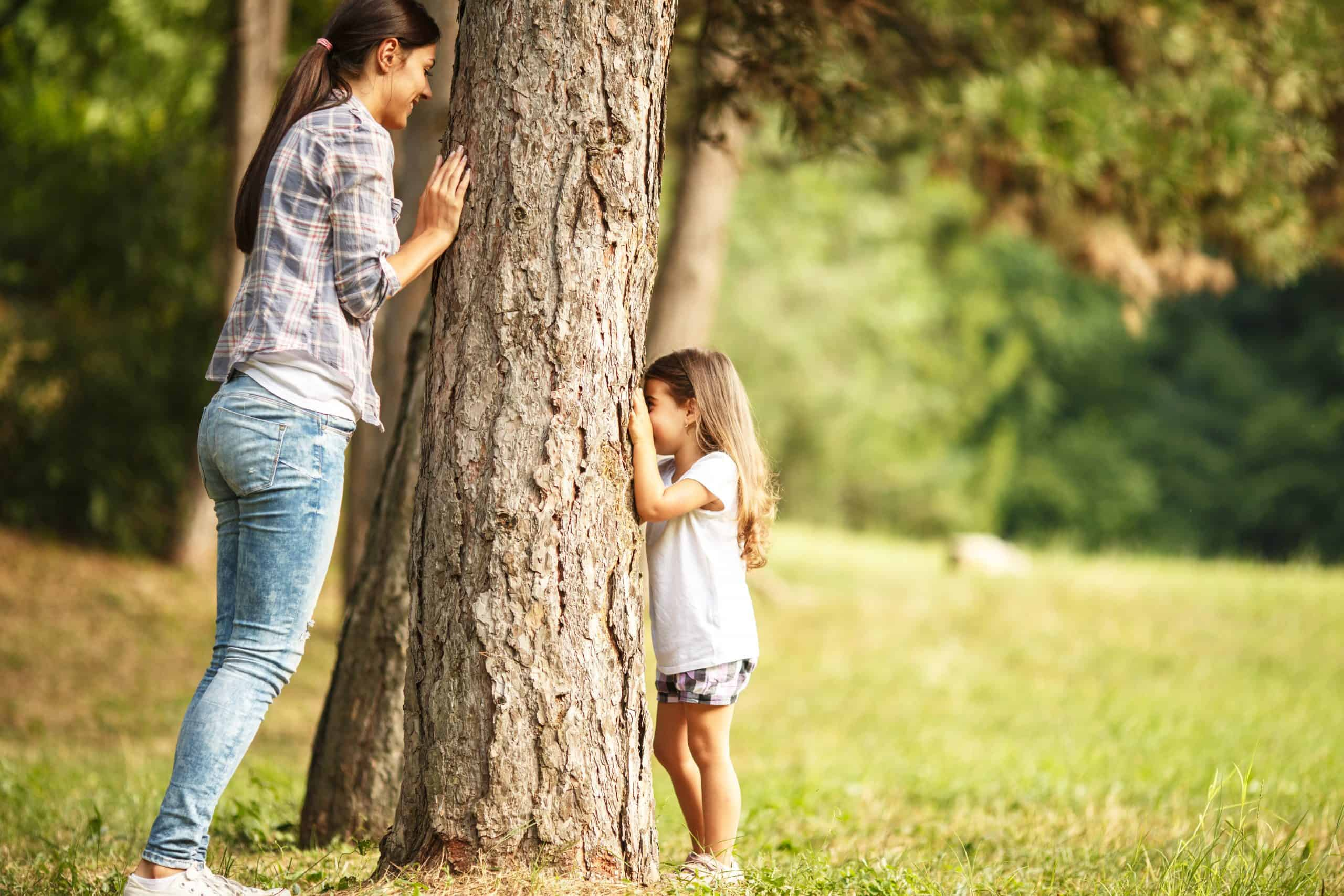 Mother and daughter play hide and seek at the park family game