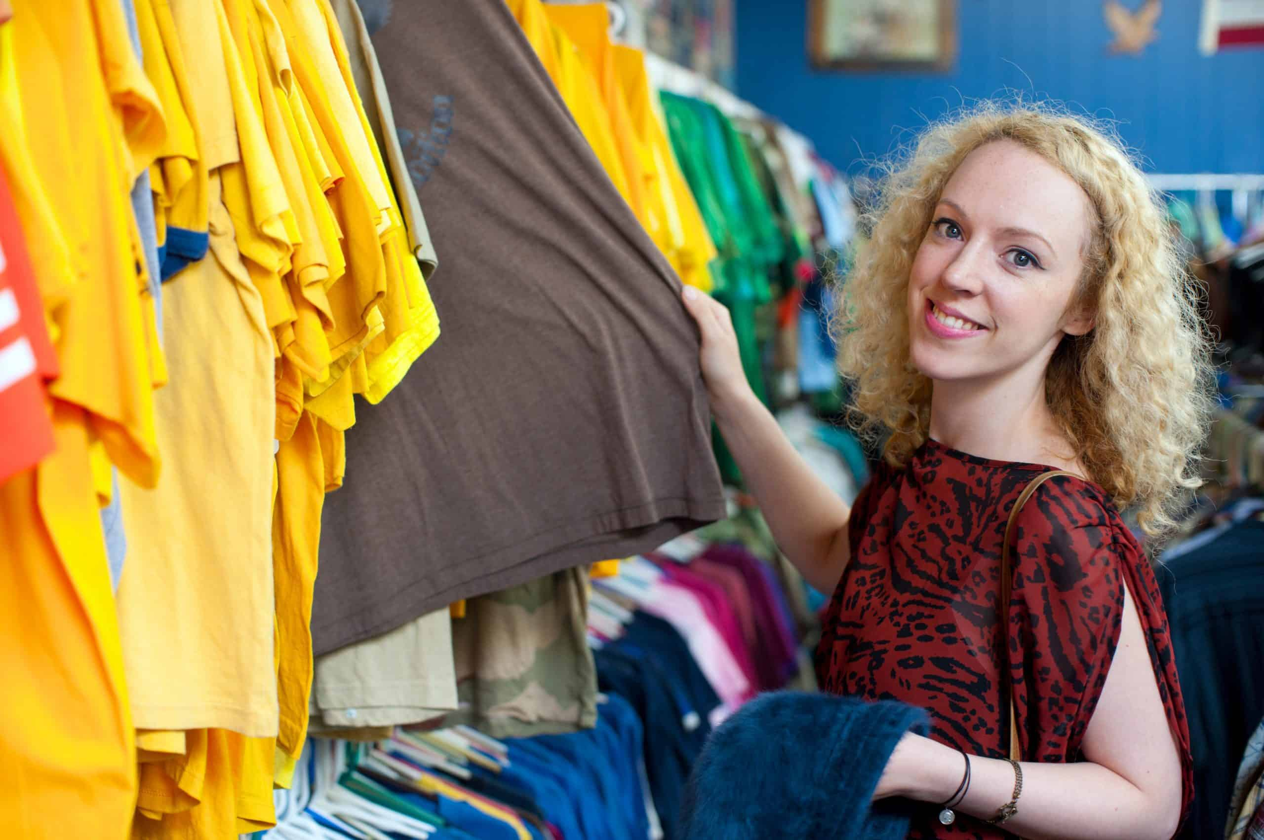 smiling girl looking through t-shirts at a thrift store