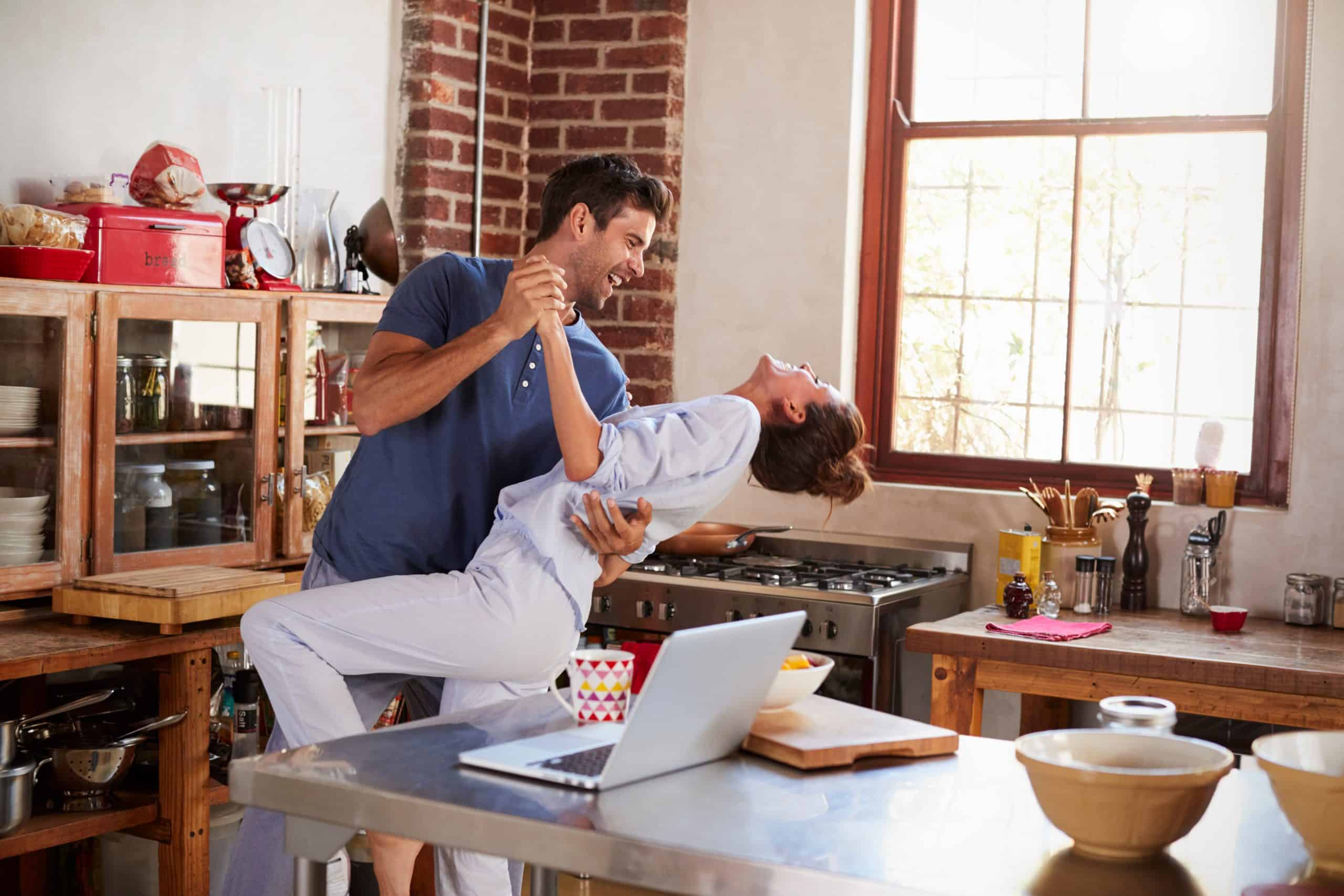 Happy Hispanic couple dancing in kitchen in the morning, dance lessons at home