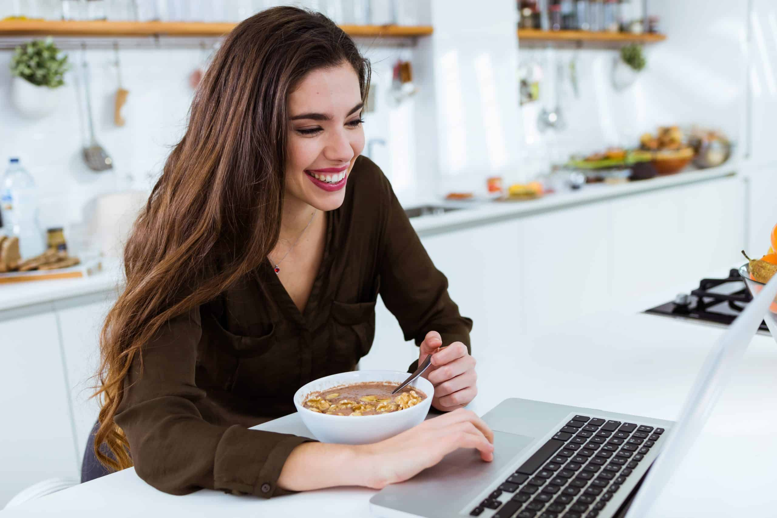 woman eating with laptop