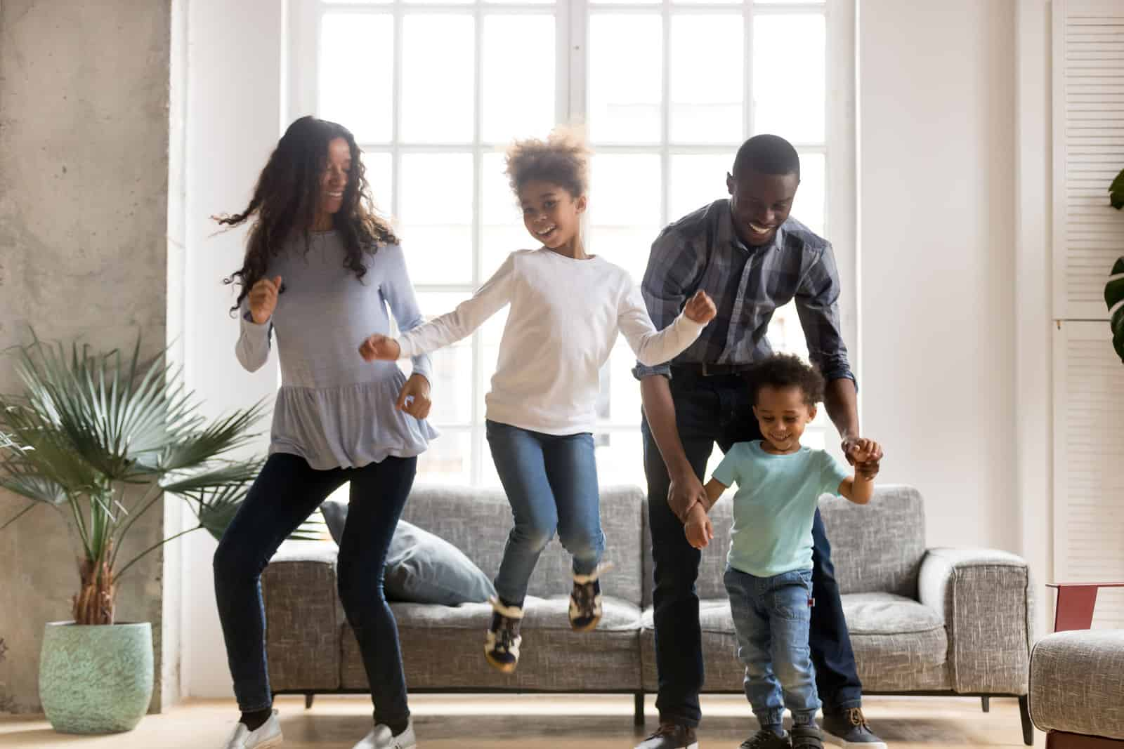 Happy black African family dancing at home, family health
