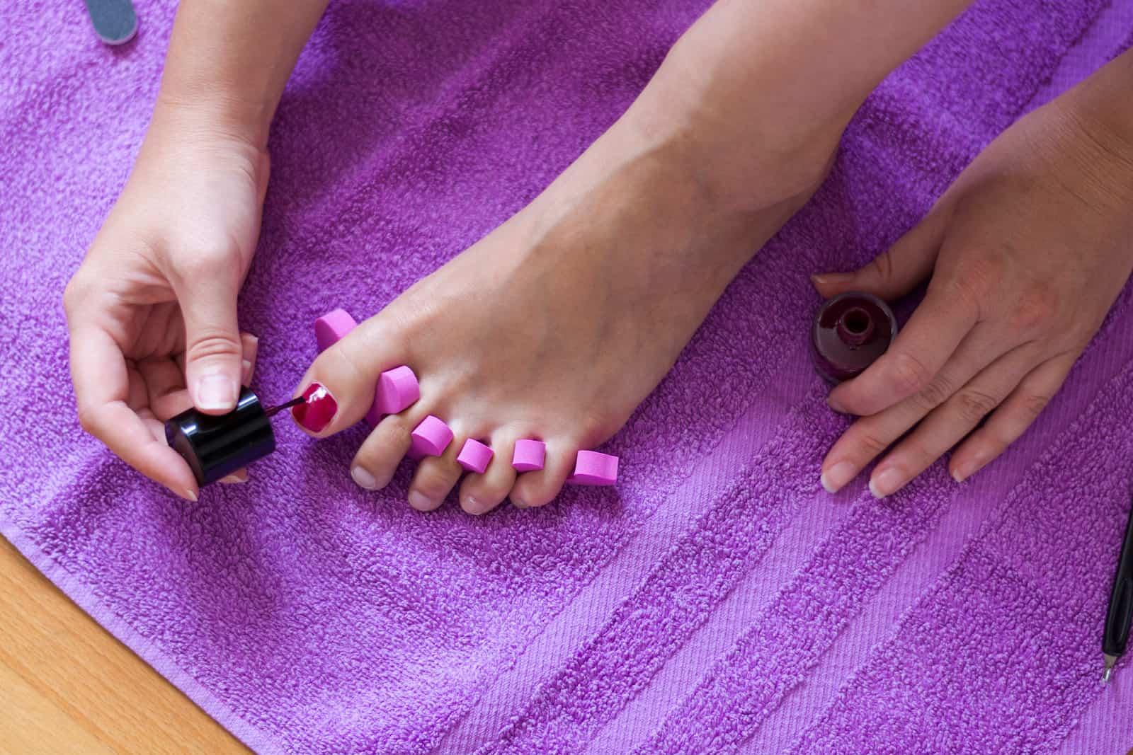 female applying nail polish at home
