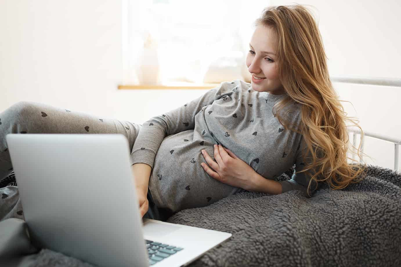 Spending pregnancy period with joy. Beautiful blonde young pregnant woman in comfy home clothes lying on bed, looking for good movie to watch on laptop, relaxing, holding hand on her belly.