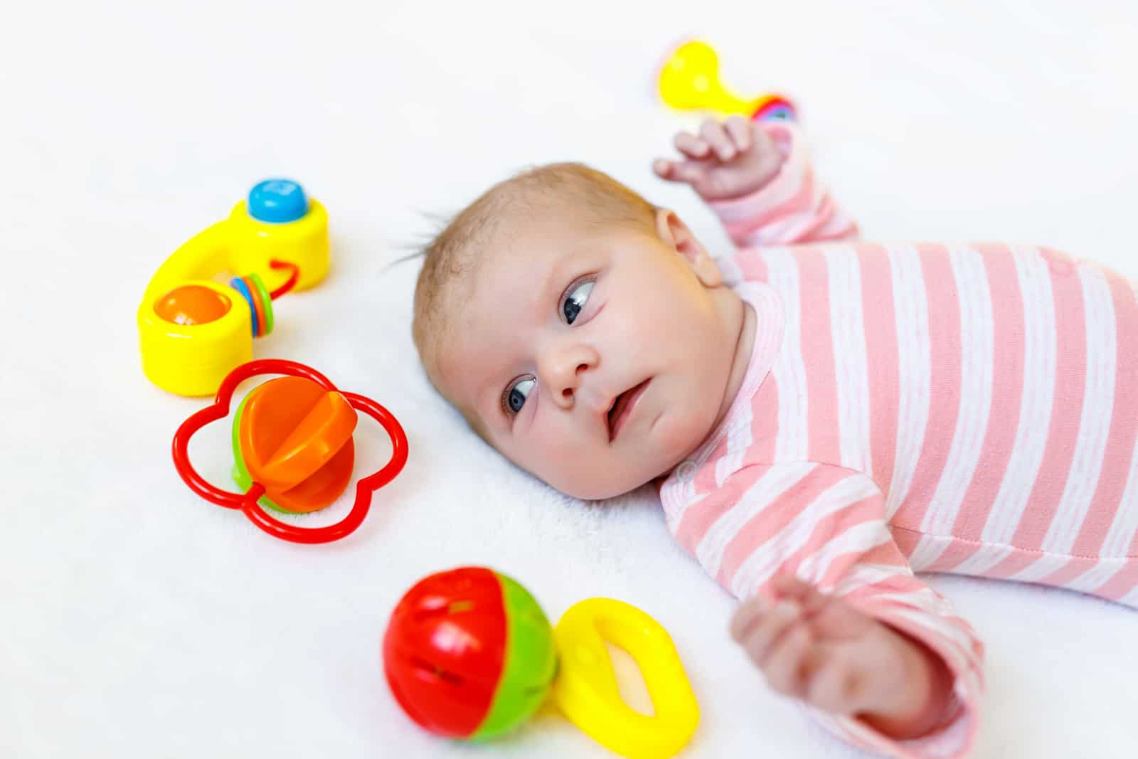 Cute baby girl playing with colorful rattle toys