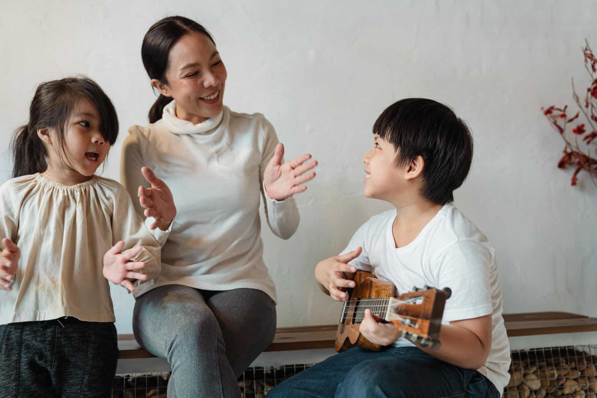 ethnic-boy-playing-ukulele-for-cheerful-sibling-and-mother-4473436