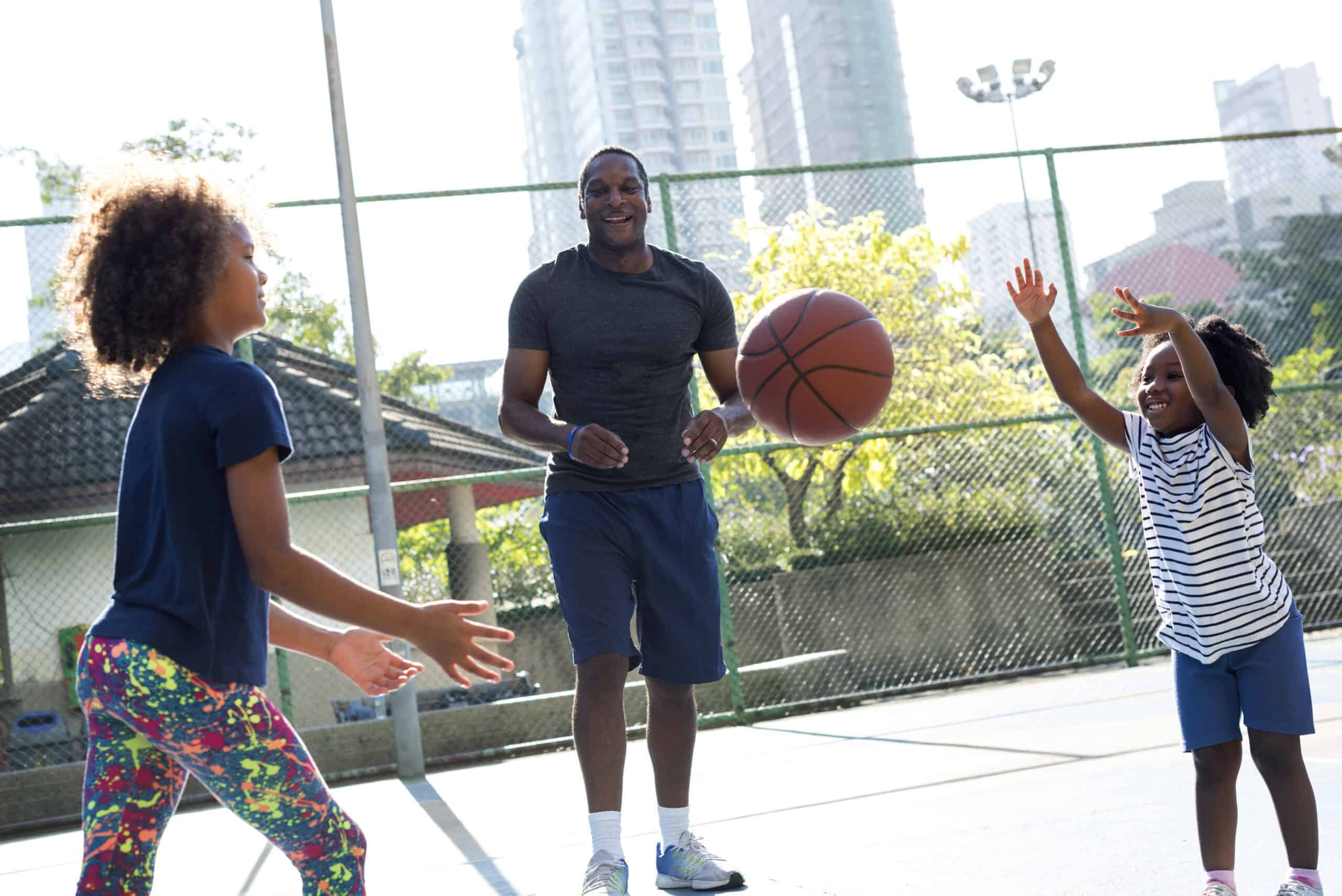 African father spending time playing basketball with his children