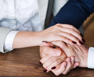 Man and woman claspe all their hands together on a wooden table