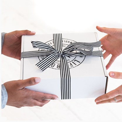 Hands passing a Lifebox wrapped in a ribbon