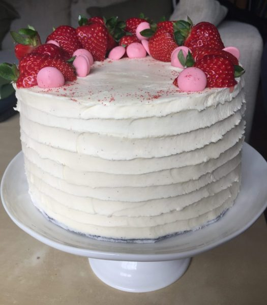 A layer cake with vanilla buttercream with a horizontal stripe pattern and topped with strawberries and pink chocolate buttons