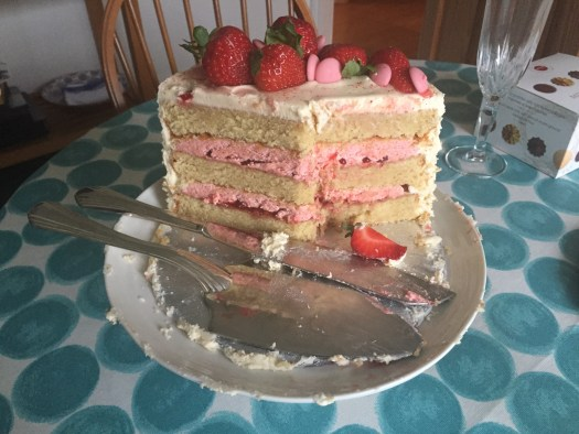 A cut away picture of a vanilla layer cake with strawberry filling and fresh strawberries on top