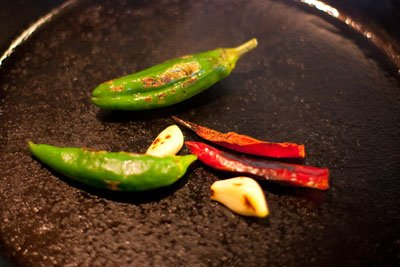 peppers and garlic in the skillet Roasted Tomato Salsa