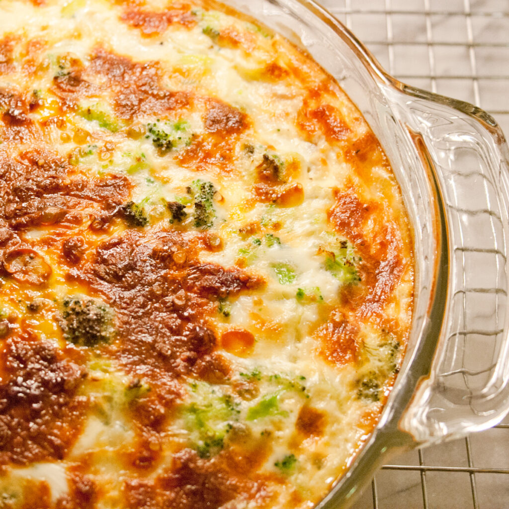 Broccoli Leek Mozzarella crustless quiche in a glass pan on a cooling rack